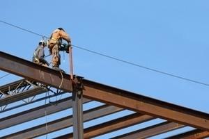 Bauhelfer arbeiten auf einer Dachkonstruktion