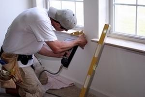 Bauhelfer arbeitet an einer Fensterbank
