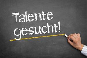 """Hand schreibt auf Tafel """"Talente gesucht"""""""