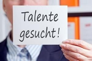 """Hit-Personal Mitarbeiter hält Blatt Papier ins Bild mit der Aufschrift: """"Talente gesucht!"""""""