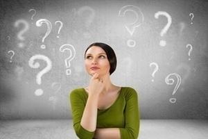 Junge Frau umgeben von Fragezeichen
