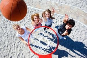 Vier Junge Menschen stehen unter einem Basketball-Korb und Werfen den Ball