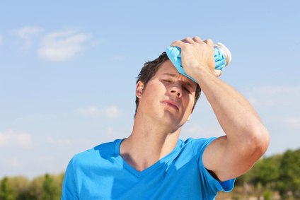 Hitze am Arbeitsplatz visualisiert durch einen Mann der sich den Kopf in der Sonne kühlt
