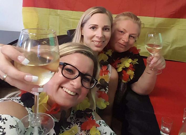 3 Damen stoßen am Arbeitsplatz auf die WM an